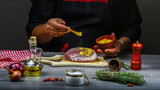 Close up of a chef hands preparing an steak with spices and vegetables. The concept of italian cooking recipe - 237677172