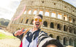 Happy tourist takina selfie at the Colosseum in Rome, Italy