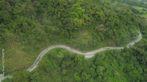 Mountain curve is a road passing along the slopes of mountains and hills covered with green forest and vegetation. Philippines, Luzon.