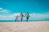happy family with child walking on tropical beach