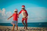 happy kids-little boy and girl- celebrating christmas on beach
