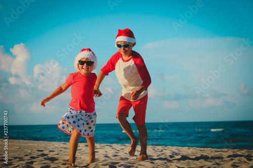 happy kids-little boy and girl- celebrating christmas on beach - 237700743