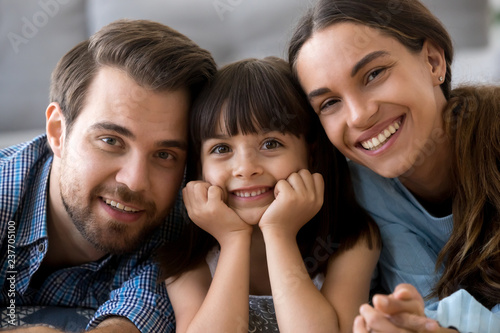 Leinwandbild Motiv Close up little cute daughter holding hands on chin lying on warm floor with young parents in living room at home married couple sweet child smiling and looking at camera. Happy diverse family concept