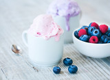 Berry ice cream in white cups and fresh berries: raspberries and blueberries