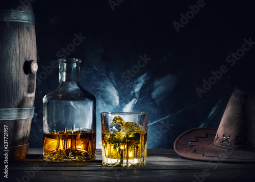Whiskey and hat and barrel on dark background