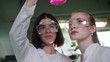 Two young women in chemical lab looking at the flask with pink liquid in it