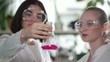 Chemical laboratory. Two young women looking at the flask with pink liquid in it and evaluate the result
