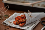 Honey roast carrots with spices and nuts on a wooden table.