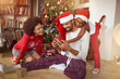 Family exchanging gifts in front of Christmas tree. - 237753150