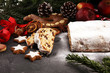Traditional European Christmas pastry, fragrant home baked stollen, with spices and dried fruit. Sliced on rustic table with xmas tree branches and decorations