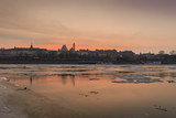 Warsaw in winter. Cityscape with the Royal Castle and the Old Town buildings on the Vistula River shore at sunset.