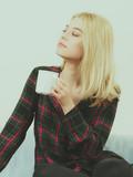 Teenage woman sitting on sofa with mug