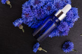 essential oil of cornflower on a dark stone background