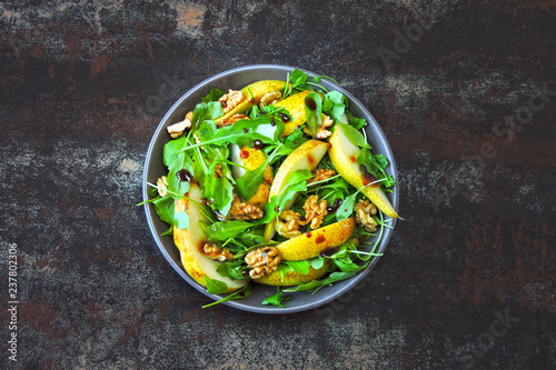 Foto Murales Healthy colorful salad with arugula and pear. Top view.