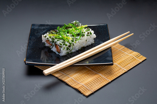 Black plate with american rolls and chopsticks