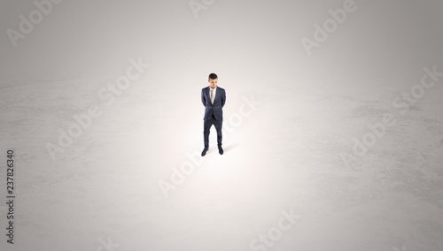 Young businessman standing alone in the middle of an empty space