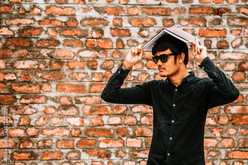 Portrait of young man with book on his head - 237828782