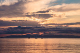 Beautiful sunset over sea with reflection in water, majestic clouds in the sky