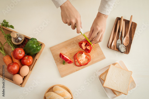 Male hands slicing fresh red bell peppers - 237835346