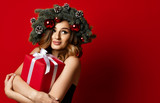 woman with Christmas spruce fir wreath with cones and new year gift box surprise present happy smiling