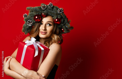 Leinwanddruck Bild woman with Christmas spruce fir wreath with cones and new year gift box surprise present happy smiling