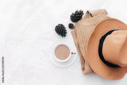 flat lay with feminine accessories: sweater, hat. Hot coffee. Cozy home autumn. Top view, copy space