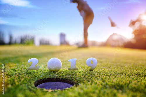 incoming year 2019, prepare by putting of woman golfer on the green, golfball mostly ready to drop into the hole of new year success, Happy new year and merry Christmas on golf course