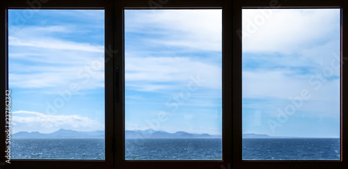 Three windows with sea view. White clouds and blue sky over the ocean. Fuerteventura, Canary Islands on the horizon. - 237862342