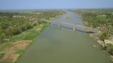 Aerial footage approaching long bridge cross green river - 237868360