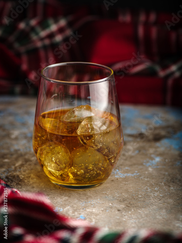 Still-life with a glass of bourbon. A glass of whiskey with ice. Concept of autumn spleen