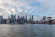 View of Manhattan with Brooklyn Bridge at sunset from the side of the pier.