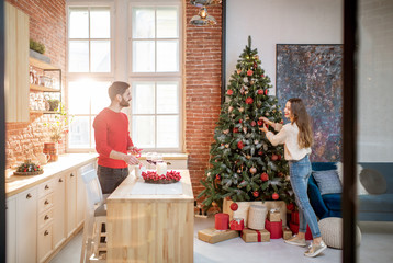 Young couple preparing for a New Year decorating their beautiful apartment standing in the dining room with Christmas tree on the background