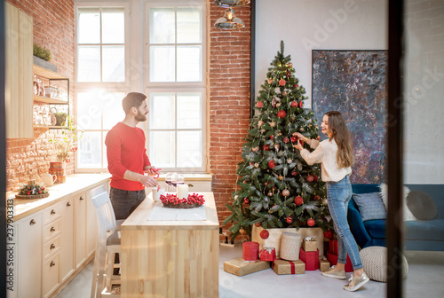 Young couple preparing for a New Year decorating their beautiful apartment standing in the dining room with Christmas tree on the background - 237903313