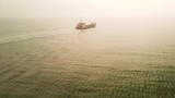 Aerial shot of a large ship out at sea transports off the coast. - 237904332