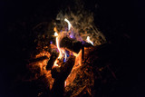 Fireplace with fire, firewoods and coal in the night, nature hiking photo