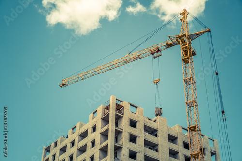 Construction crane and building against blue sky