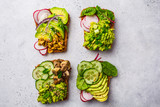 Avocado toasts with different toppings, top view, white background.
