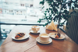 Breakfast for two with coffee and croissant on the table by the window in modern cafe, copy space
