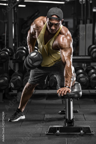 Muscular man working out in gym doing exercises for back. Single Arm Dumbbell Row - 237942164