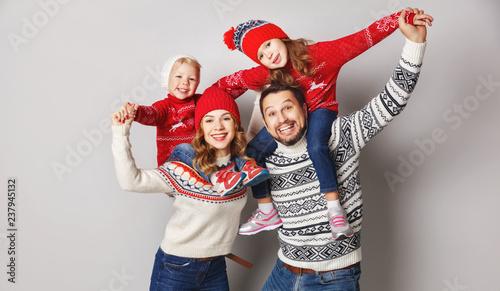 szczęśliwa rodzina matka, ojciec i dzieci w czapki z dzianiny i swetry na szarym tle