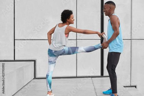 Czarny pozytywny instruktor męski pomaga stażystce w wykonywaniu ćwiczeń na elastyczność, stanąć przy schodach na białej ścianie, mieć szczęśliwe słowa, ubrane w odzież sportową. Ludzie, sport i koncepcja traning