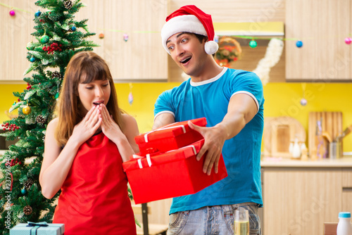 Leinwanddruck Bild Young couple celebrating Christmas in kitchen