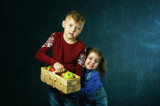 Brother and sister holding a basket of apples on a dark background - 237981382