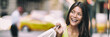 Shopping in New York City Asian woman smiling happy holding shopping bag panoramic banner background. Girl looking to the side with yellow cabs taxi cars header.