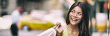 Shopping in New York City Asian woman smiling happy holding shopping bag panoramic banner background. Girl looking to the side with yellow cabs taxi cars header. - 237986330