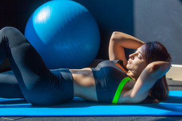 Side view image of young fit woman exercising in a gym lying on mat doing leg raising and twisting exercises.