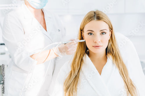 Zobacz obraz Female patient undergoing facial anti-aging procedure in beauty centre. Rejuvenating facial gas liquid treatment. Professional doctor dermatologist stroking with cosmetic apparatus woman s face skin