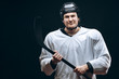 Hockey player wearing white protective gear and black helmet posing at camera with the hockey stick. Isolated on black background.