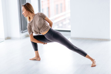 flexible girl leaning on her leg and crossing her rams behind the back. flexibility concept. side view full length photo