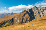 Trekker hiking in autumn alps with superb mountain plates in behind, Grossglockner area, Tyrol, Austria - 238007983
